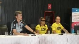 Imagem com Adriana, Roseni e Vicente, sentados à enorme mesa do auditório, falando ao público